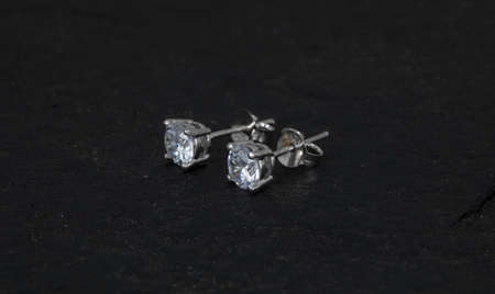 Close up of diamond earrings isolated on black rock background 免版税图像