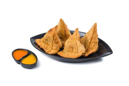 Indian Fried Food Samosa with chutney isolated on white Standard-Bild