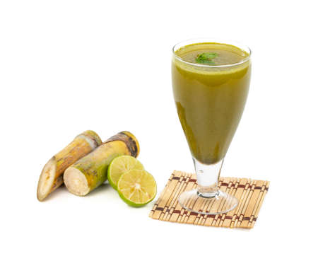Fresh sugar cane juice in glass with cut pieces cane on isolate background