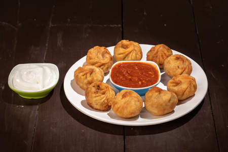 Nepalese traditional food dumpling momos served with tomato chutney and fresh yogurt
