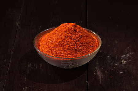 Red chilli powder made from Indian dried red chillies, Indian spice and Indian food ingredient on wooden Background