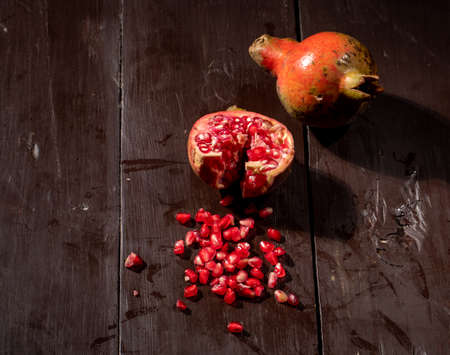 Ripe and juicy pomegranate in basket on wooden table