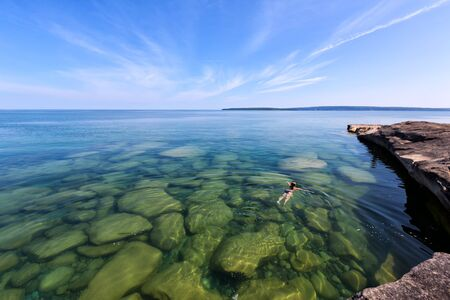 upper peninsula: A girl swims in Lake Superior in the upper peninsula of Lake Michigan. Rocks are visable through the glass like, pristine waters. Pictured Rocks National Lakeshore is in the distance.