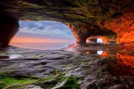 The walls of this sea cave radiate a vivid red from the sun setting over Lake Superior. The Pictured Rocks area near Munising Michigan has many interesting formations along it's shoreline.