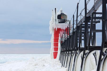 lake michigan lighthouse: Lago Michigans aguas tormentosas han creado una cubierta de hielo sobre la luz del rompeolas sur del asilo en South Haven Michigan. Hielo encierra la pasarela, as�, para hacer una imagen escalofriante en este d�a con la congelaci�n escalofr�os viento a lo largo de la costa del Lago Michigan Foto de archivo