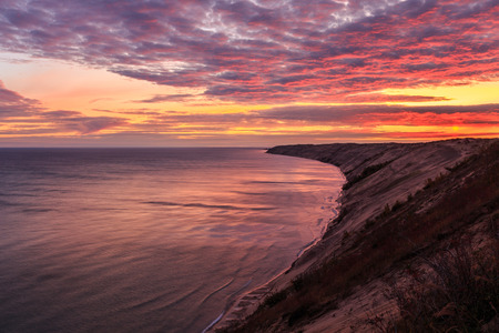pictured: A spectacular sunrise over Grand Sable Dunes near Grand Marais, Michigan. The Log Slide Overlook is part of Pictured Rocks National Lakeshore, located between Munising and Grand Marais.