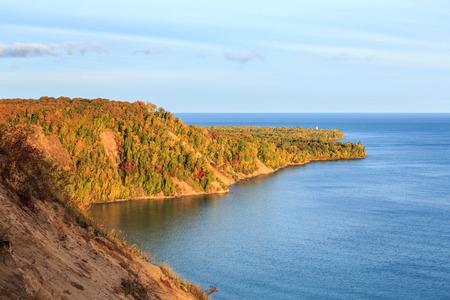 sable: Au Sable Point in Autumn - Sunrise illuminates autumn foliage surrounding the Au Sable Point Lighthouse with Lake Superior in the background.