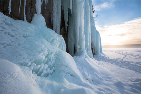 michigan snow: A gentle sunrise splays its colored hues across blue tinted ice curtains on Grand Island, near Munising Michigan. Nature provides these ice formations with snow runoff that drips and freezes over the rocky cliff faces along the shoreline Stock Photo