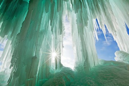 pictured: Emerald colored ice curtains drape from the cliffs along the shores of Lake Superiors Grand Island. Just off shore from Pictured Rocks National Lakeshore in Munising, Michigan