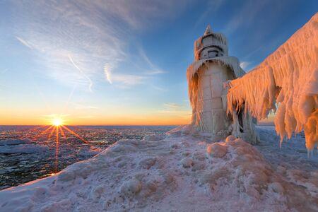 lake michigan lighthouse: Una puesta de sol de invierno del lago Michigan ilumina los hielos que encapsula el muelle norte de San Jos�. Foto de archivo