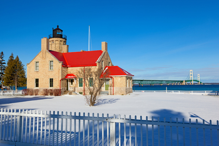 mackinac: Old Mackinac Point Lighthouse in Mackinaw city sits in a blanket of snow on this sunny Michigan day. The Mackinac Bridge is visible in the background.