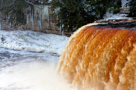 upper peninsula: Caramel colored waters rush over Tahquamenon Falls as huge icicles drape the rockface and form from rising mist in this winter scene. Tahquamenon Falls State Park in the Upper Peninsula of Michigan Stock Photo
