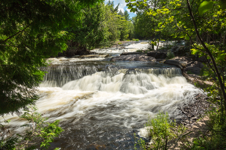 Upper Bond Falls in the Upper Peninsula of Michigan on a bright, summer day. The Ontonagon river runs swiftly over this waterfall Stock Photo - 82320391