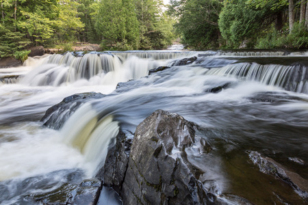 Upper Bond Falls in the Upper Peninsula of Michigan. The Ontonagon River flows swiftly over the basalt rock. Фото со стока