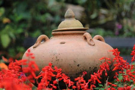olla barro: cazuela de barro en la flor Foto de archivo