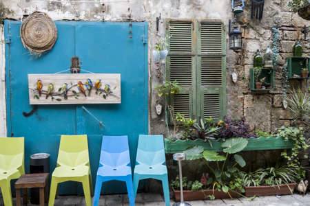 Colour chairs on blue door in front of caffe, Israel