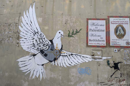 Jerusalem, Israel - 12/15/2019: graffiti on the wall between border of Israel and Palestine, some of them by Banksy Publikacyjne