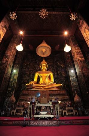 A seated golden Buddha at Wat Suthat Bangkok, Thailand. Stock Photo
