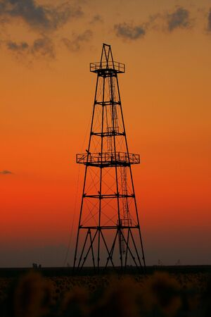Abandoned oil well profiled on beautiful sunset