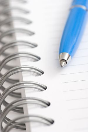 blue pen on white spiral notebook Reklamní fotografie