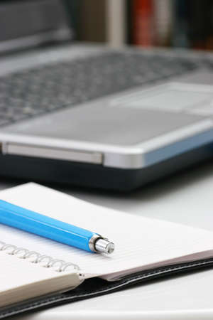 blue pen on notebook and laptop computer