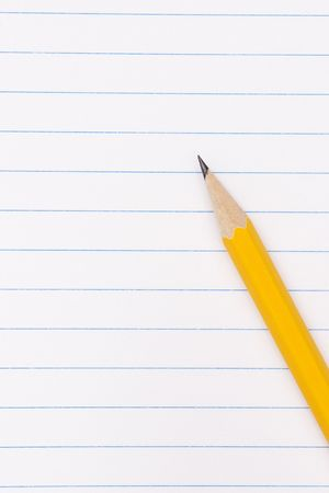 yellow pencil on clean lined notebook photo