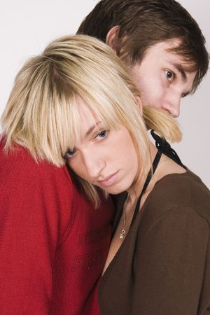 young man hugs and comforts young female