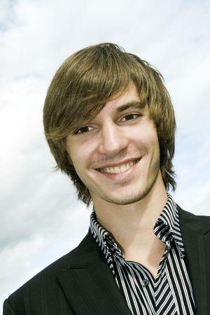 Satisfied smiling businessman  on sky background