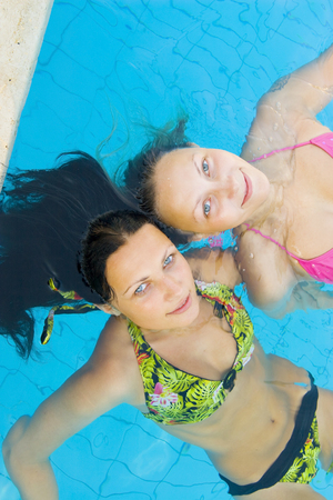 Two beautiul girls splashing around and enjoying the sun in a swimming pool Stock Photo - 1504499