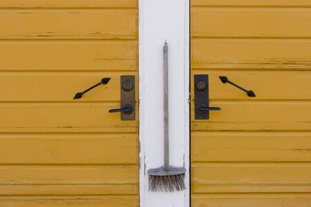 swept: doors of an old wooden house with broom