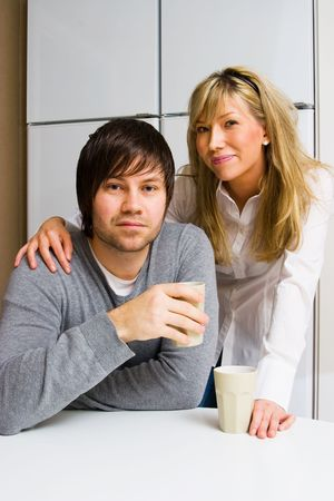 Young happy couple in the kitchen photo