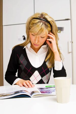 young woman reading magazine in the kitchen