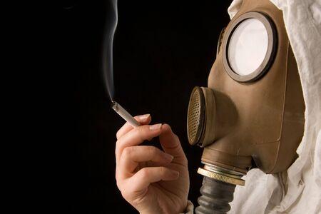 habbit: Person in gas mask smoking cigarette on dark background Stock Photo