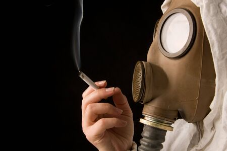 Person in gas mask smoking cigarette on dark background Standard-Bild