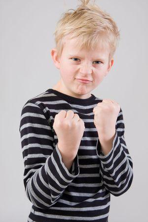 ni�o parado: Retrato de un peque�o muchacho enojado que est� parado en la posici�n de la lucha