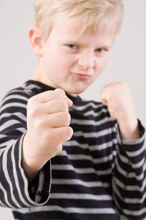 ni�o parado: Retrato de un poco enojado muchacho de pie en posici�n de lucha