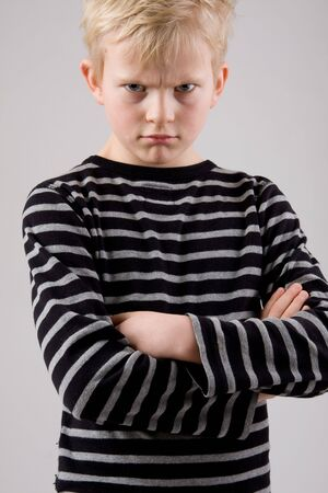 Portrait of a angry little boy posing on white background photo