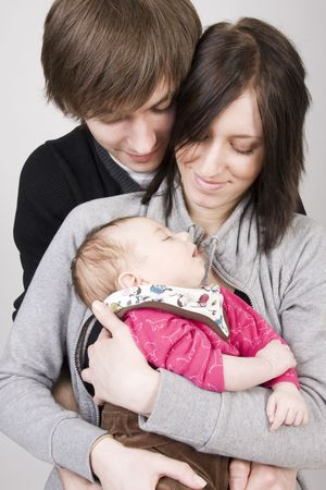 Happy young family (father, mother and cute little baby girl)  photo