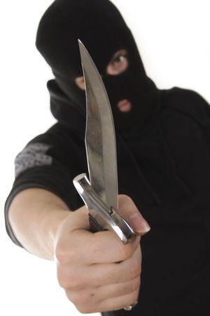 evil criminal with a knife wearing balaclava Standard-Bild