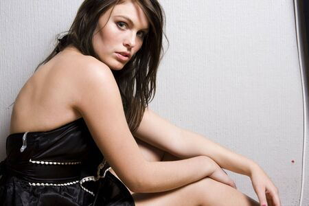 Portrait of young beautiful woman sitting on the floor photo