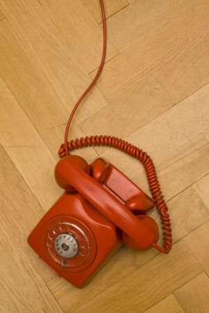 old red telephone laying on the floor