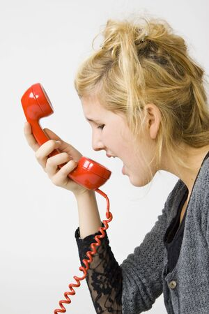 young teenage girl yelling into red vintage telephone receiver photo