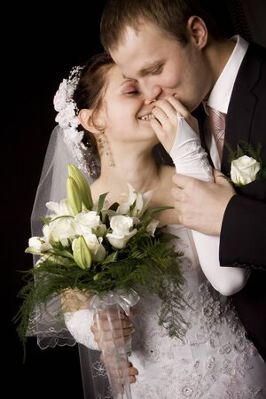 Bride and groom kissing on black background