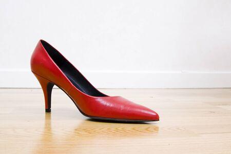 entice: fashionable female shoe on wooden floor Stock Photo