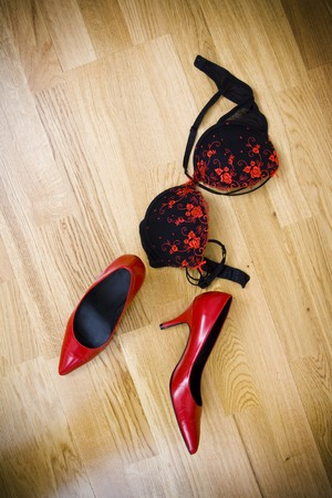 fashionable female shoes and bra on wooden floor Standard-Bild