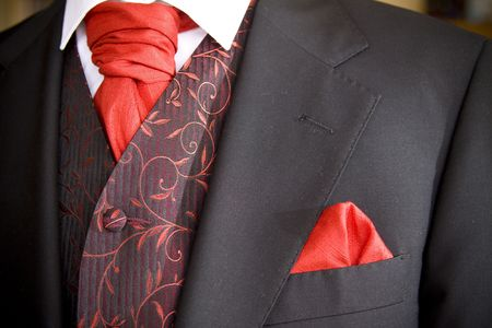 suit jacket of groom and red cravat ascot tie  photo