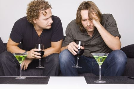 two friends drinking at home (grimacing) Standard-Bild