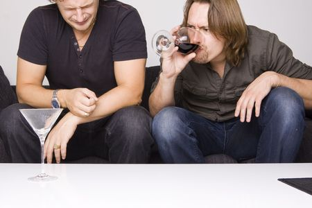 two friends drinking at home (grimacing) Stock Photo