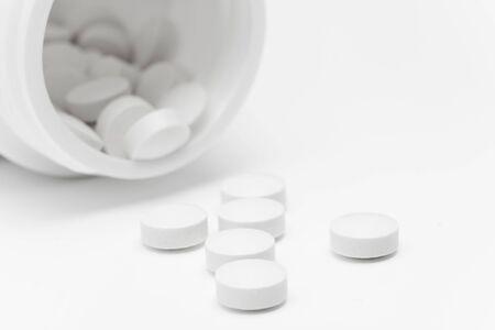 pill bottle: Spilled pills from open prescription medication bottle