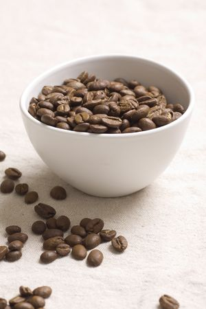Roasted coffee beans in a white bowl on jute sacking